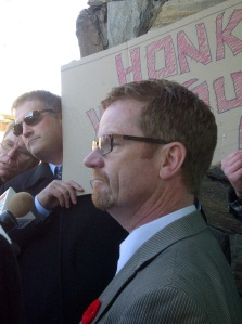 MLA Terry Lake talks with protesters outside his office Friday.